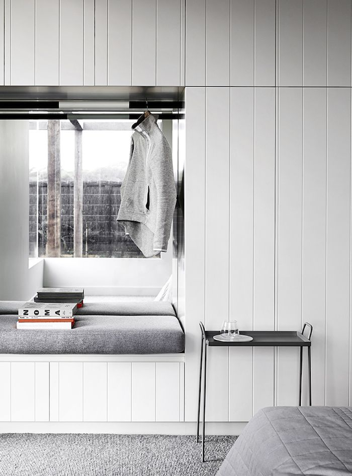 Bedroom: built-in wardrobe with white wooden vertical panelling on handleless doors, seating nook/recess with clothes rail and mirror, light grey low-pile carpet, grey quilted bed linen