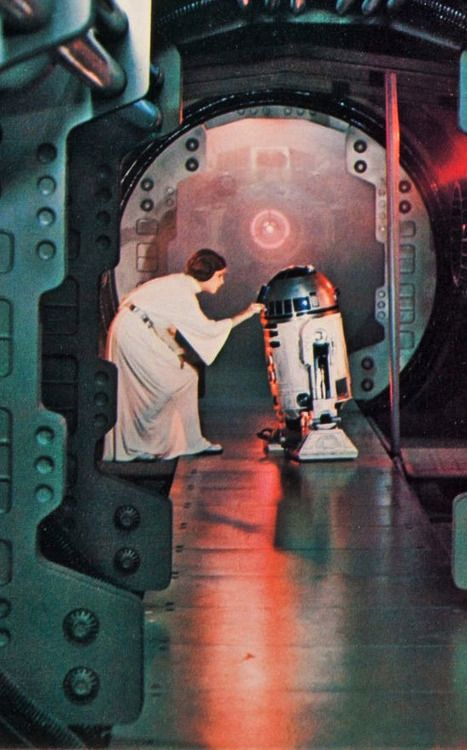 RIP Carrie Fisher>Princess Leia places plans for the Death Star into the robot R2-D2.