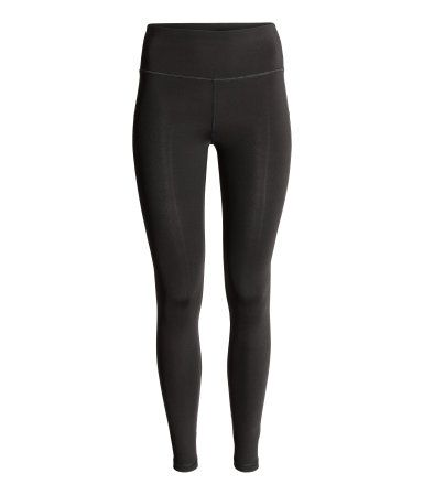 Sports tights in slightly thicker, fast-drying functional fabric with sculpting effect on tummy, hips, seat, and thighs. High waist with wide waistband, taped seams along outer legs, and contrasting back section.