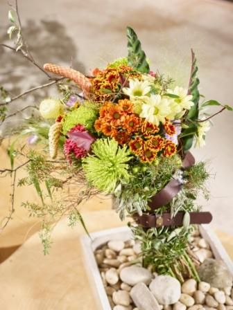"""Herbstlicher Blütenstrauß Autumn Breeze Diese, wie natürlich verwehten Sträuße in aktueller Bundle-Optik begleiten uns durch den Herbst. Mit ihrer asymmetrischen Form, ihrer herbstlichen Blütenfülle und ihrem unempfindlich-robusten Look sind diese herb nach Salbei und Rosmarin duftenden """"Naturburschen"""" echte Eyecatcher. In der schlichten Naturstein-Schale erhält dieses Blumenarrangement einen besonderen Kick durch die Taillierung mit einem kräftigen Ledergürtel."""