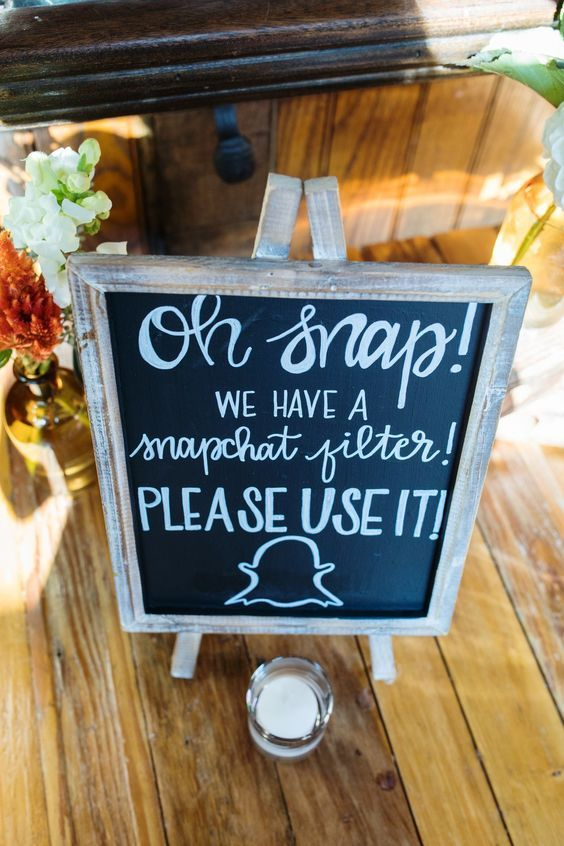 A Snapchat filter sign from Teona Ostrov's wedding. Use a wedding snapchat filter instead of a hashtag to encourage guests to document your big day. Make a DIY chalkboard sign so everyone will know you have a snapchat filter.