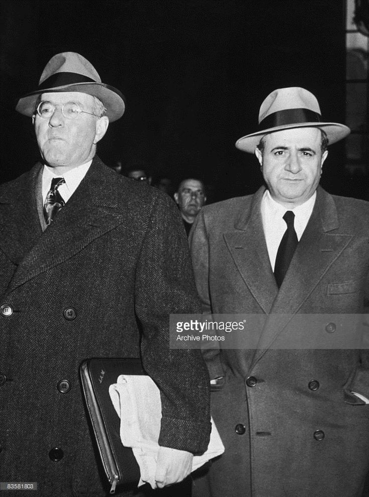 Albert Anastasia (1902 - 1957, right), the chief executioner for the enforcement side of the National Syndicate, Murder Inc. arrives at County Courthouse with his attorney to testify before the New York State Crime Commission probing waterfront crime, 1940s.