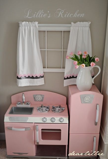 Curtains and flowers added to a wooden play kitchen. Such a cute idea for a playroom.