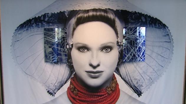 Een enorm portret van een Zeeuws meisje waarbij de spiegels aan de Bevelandse kap, in dit geval foto's zijn, van hoogspanningsmasten. Ze zijn gemaakt door Leon van der Flier uit Yerseke en hangen bij de ingang van het kantoor van Delta in Goes