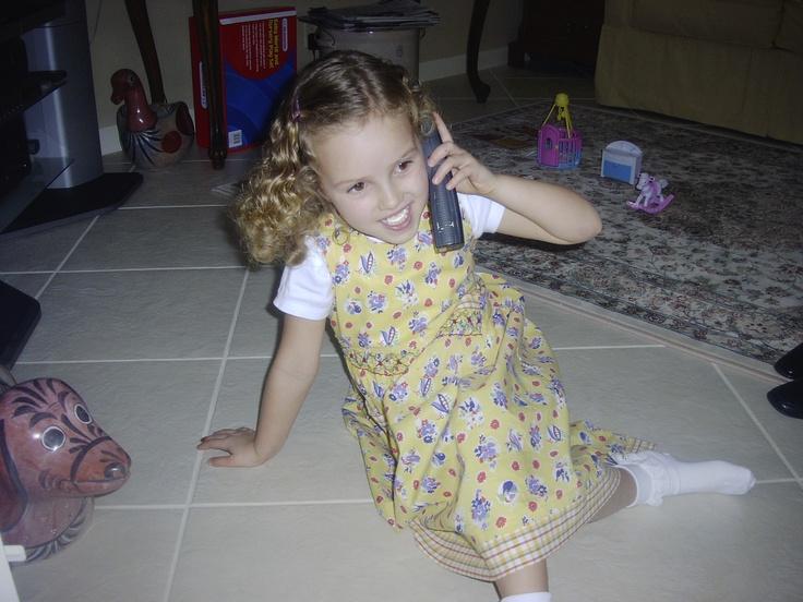 Nella foto, sono con nessuno. Avevo sei anni. Quando ero piccola, parlavo sul telefonini ogni giorni perche' mi piaceva parlare molto. Io non sono cambiata da quando ero piccola perche' io parlo molto. Nella foto, assomigliavo mia nonna da bambina. Portavo un vestito giallo e i calzini bianchi. Avevo i capelli ricci e le pelle bianche. Ero nella casa degli miei nonni. Ci erano molti giocattoli sul pavimento. Mi sentivo molto loquace. Sono restata con mia nonna.
