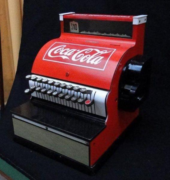 Colecionismo - Máquina registradora importada, restaurada e modernizada com decoração Coca-Cola. Em pesado metal, sobre caixa com tampo de mármore negro e compartimento para cédulas e moedas. Med. 43 x 39 x 40 cm