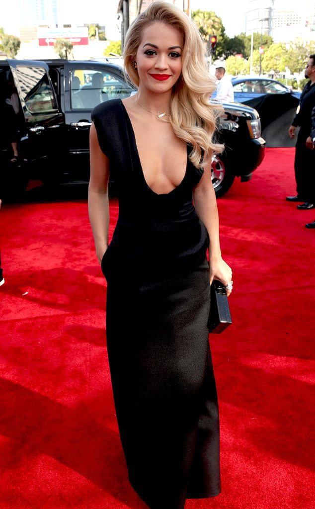 Rita Ora shows off some major cleavage in a low-cut black dress.