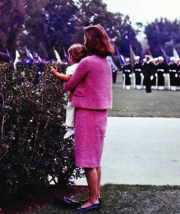 Here, Jackie wears the suit while holding John Jr. as she awaits the arrival of President Ahmed Ben Bella of Algeria (October 1962).