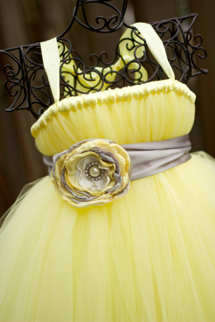 OMG!! This dress is one of our favs! Made is pastel yellow tulle and featuring a silver grey sash with a handmade flower. Our flowers are made with layers of silk, satin and lace and this one has layers in yellow, cream and grey. Perfect for flower girls! And the sash can be used after the [...]