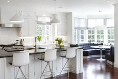 Iconic Saarinen Table for Interior Design with Relaxed Impression: White Kitchen Cabinet And Marble Backsplash With Saarinen Table Also Kitchen Faucet With Barstools Plus White Tulip Table And Window Seating With Chandelier Plus Wood Floors And Ikea Dinner Table
