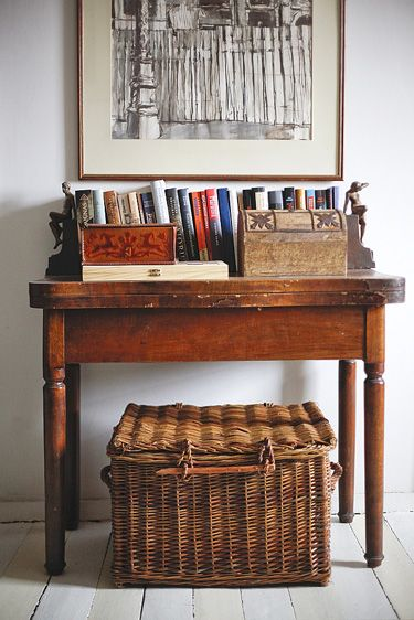 White floors, aged wood, willow basket and books - lovely entry way storage and style