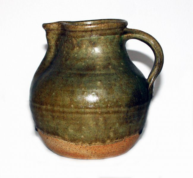 Barry Brickell Stoneware jug, with green glaze, applied strap handle, impressed potters marks. H. 200mm