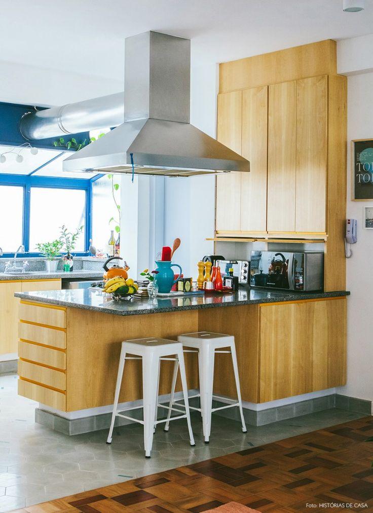 Cozinha com marcenaria feita sob medida, esquadrias pintadas de azul e piso de ladrilho hidráulico.