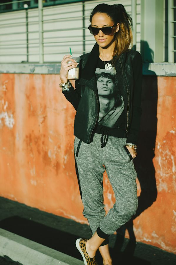 Comprar ropa de este look:  https://lookastic.es/moda-mujer/looks/chaleco-camiseta-con-cuello-barco-pantalon-de-chandal-mocasin-gafas-de-sol-colgante-pulsera/6231  — Gafas de Sol Negras  — Colgante Plateado  — Pulsera Plateada  — Camiseta con Cuello Barco Estampada Negra  — Chaleco de Cuero Negro  — Pantalón de Chándal Gris  — Mocasín de Ante de Leopardo Marrón Claro