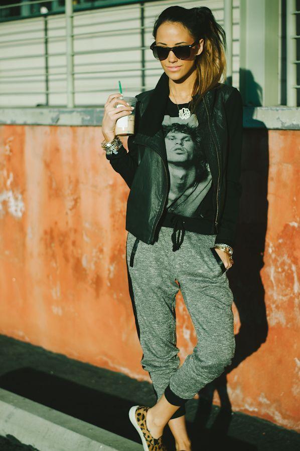 Shop this look on Lookastic: https://lookastic.com/women/looks/vest-crew-neck-t-shirt-sweatpants-loafers-sunglasses-pendant-bracelet/6231 — Black Sunglasses — Silver Pendant — Silver Bracelet — Black Print Crew-neck T-shirt — Black Leather Vest — Grey Sweatpants — Tan Leopard Suede Loafers