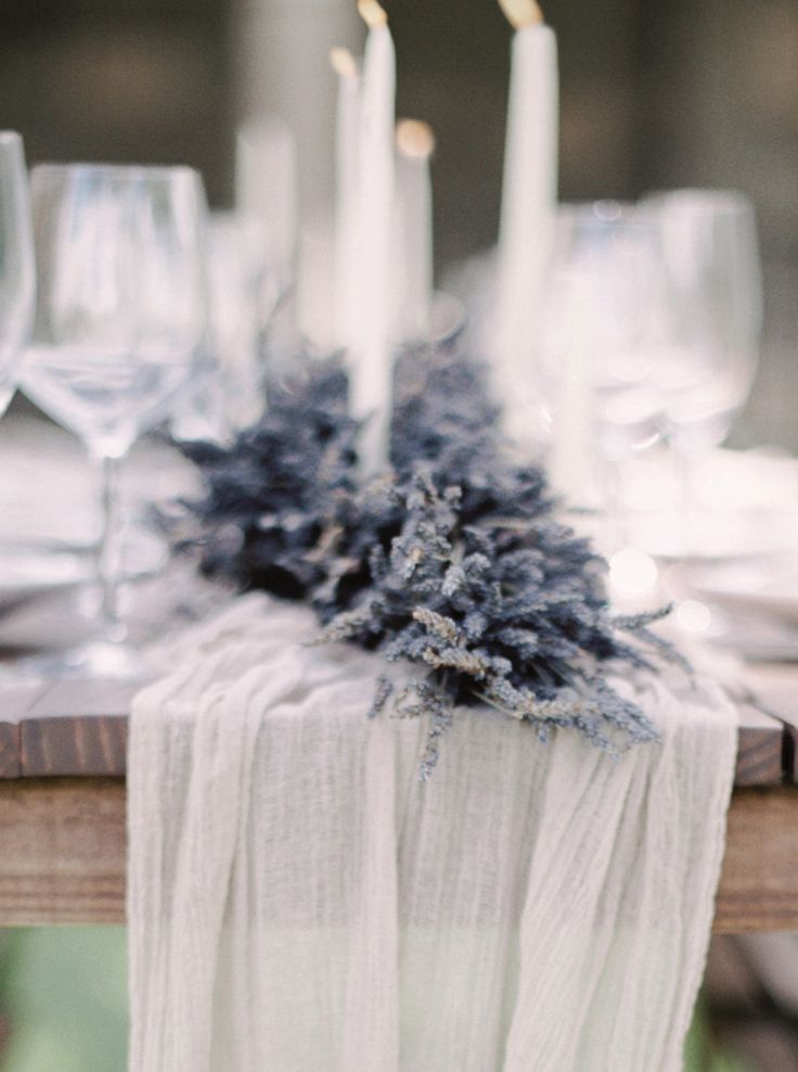 Centerpiece of lavender garland with a silk table runner and taper candles. Silk runner by Silk & Willow, florals by Flutter Fete, image by Melanie Gabrielle.