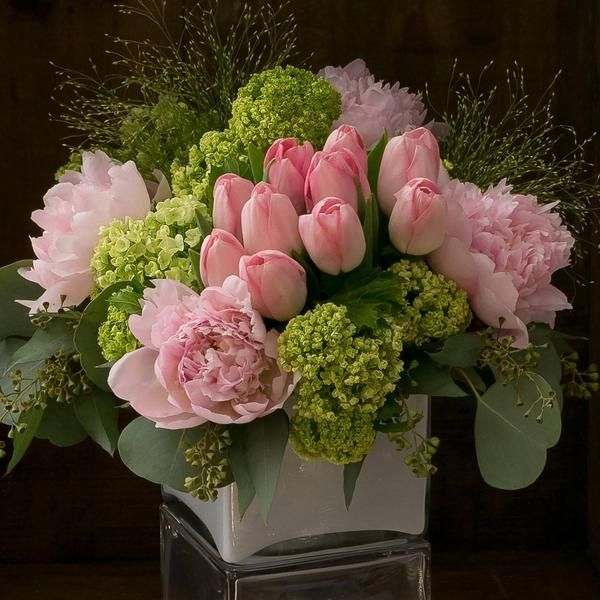 A garden of premium springtime classics is all dressed up in shades of blush-pale pink peonies, delicate pink french tulips, and green viburnum. Finished...