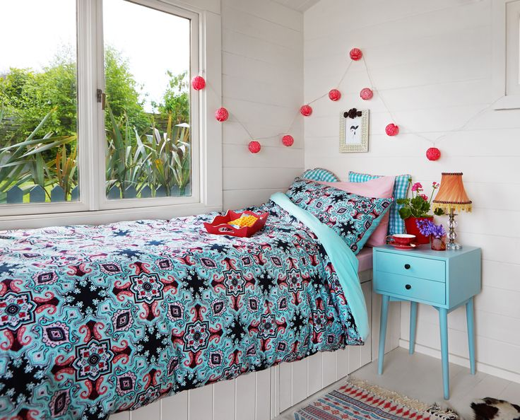 Carolyn Donnelly eclectic bedspread, pillows, blue side table and tassel lamp