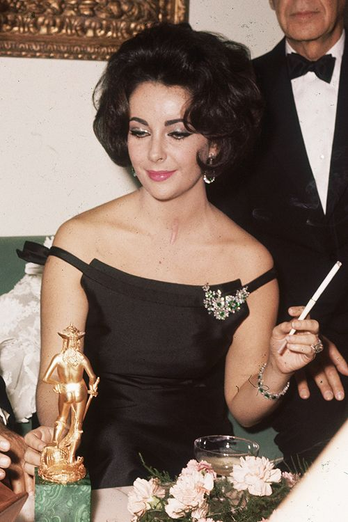 Elizabeth Taylor, 1962 - LBD with her signature bejeweled brooch.