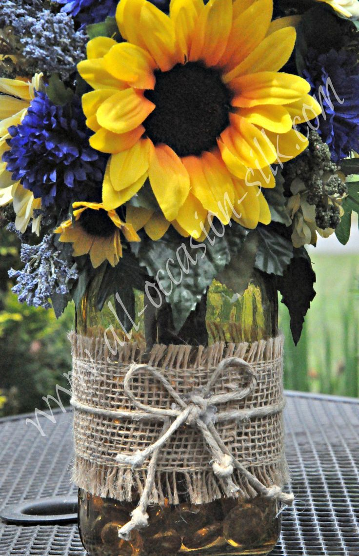 Rustic-style centerpiece featuring sunflowers, blue delphinium, blue pom poms, and gerbera daisies in a yellow-tinted mason jar tied with burlap and twine  i like the burlap it fits ur country theme