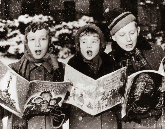Three young carol singers give their rendering of a Christmas song in the falling snow. (Photo by Keystone/Getty Images). 1957 vintage everyday