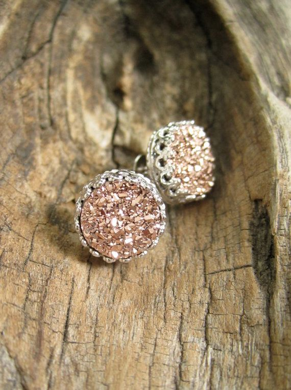 Gorgeous, rose gold druzy quartz coins are hand set inside intricate sterling silver ear posts with backs.  Natural, druzy stones are vapor coated with titanium to bring out a brilliant, consistent rose gold (pink gold) color. Each stud is 10mm round. Sterling silver bezel setting boasts intricate crown detailing, polished to a high shine for a beautiful contrast in tone and texture. They have been rhodium plated to protect them from tarnish, and they are nickel free and suitable for…