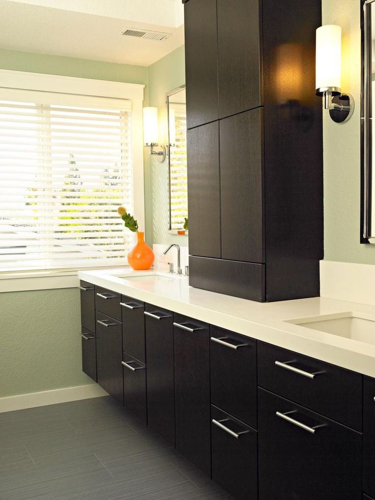 A room-length vanity is divided by a large, black cabinet with four doors in this contemporary bathroom. Black under-counter cabinets and drawers provide plenty of storage, while two built-in sinks, wall mirrors, and wall sconce lighting complete the design