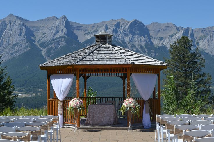 Tall wedding ceremony arrangements for an outdoor gazebo wedding at Silvertip Resort in Canmore, Alberta. Arrangements had a mixture of pink and blush roses, white hydrangea, curly willow and hanging green amaranthus.  Flowers by Janie- Calgary and Canmore Wedding Florist   www.flowersbyjanie.com
