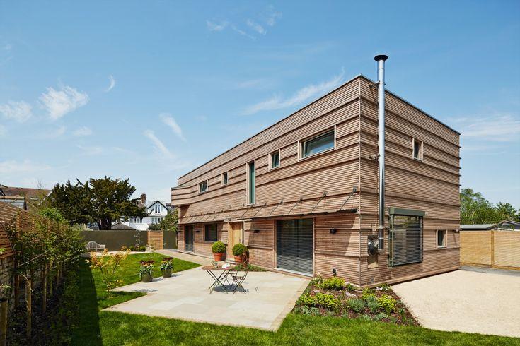 Moderne Holzhaus-Architektur mit Flachdach - Einfamilienhaus Treehouse von Baufritz - Fertighaus bauen mit moderner Holz Fassade - HausbauDirekt.de