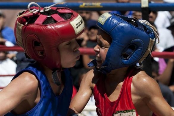 Erick Villanueva (R), 9, who was left homeless after the December 2010 torrential rains, and Luis Flores, 10, exchange punches during their fight in a Olympics-style street boxing championships in Caracas February 19, 2011.  REUTERS/Carlos Garcia Rawlins