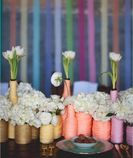 Give those old beer bottles a second life by covering them with multicolored yarn. Start by attaching the yarn with a little bit of hot glue; when the bottle is sufficiently covered, tuck the end of the yarn in. From Wedding Chicks