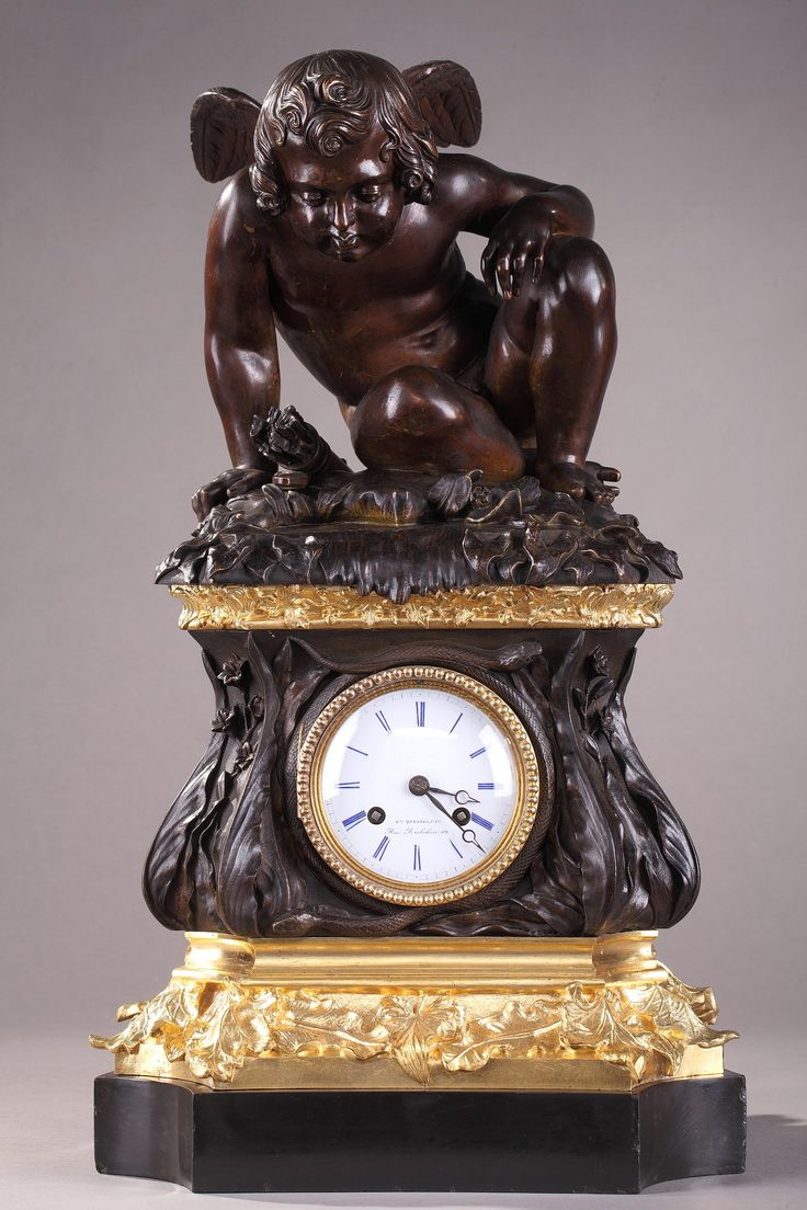"""Mid-19th century mantel clock in gilt and patinated bronze featuring a winged Cupid on a terrace sculpted with flowers, foliages and animals. The white enamelled dial, with blue Roman numerals for hours, is highlighted with a frieze of ormolu pearls and patinated bronze snakes. It is marked: """"Ene QUESNEL & Cie Rue Richelieu 112""""."""