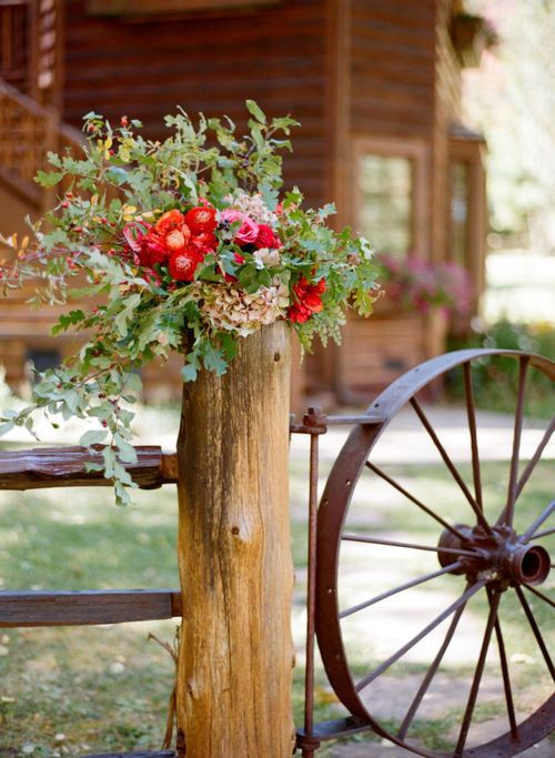 Wagon wheel gate, flowers on fence post.
