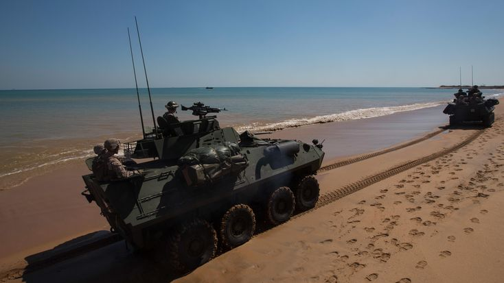 U.S. Marines in LAV-25 Light Armored Vehicles drive along the shore following an amphibious assault at Fog Bay, Australia, July 11, 2015. US Marine Corps