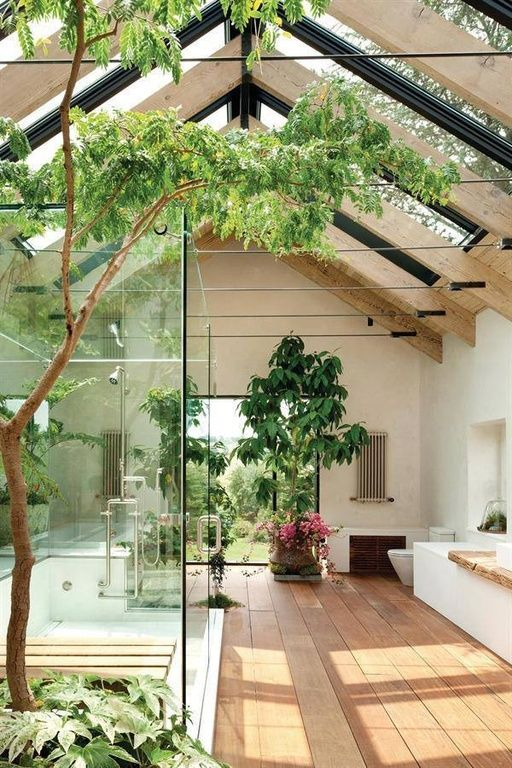 This bathroom has natural wood floors and a terrarium feel to it with all the houseplants. Exposed wood beams  and skylights open up the room and provide ample natural lighting.