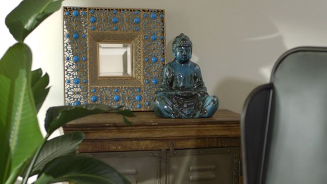 APRÈS : Un buffet en bois importé a aussi été ajouté à la droite du canapé sur lequel des miroirs et des objets zen et exotiques sont disposés.