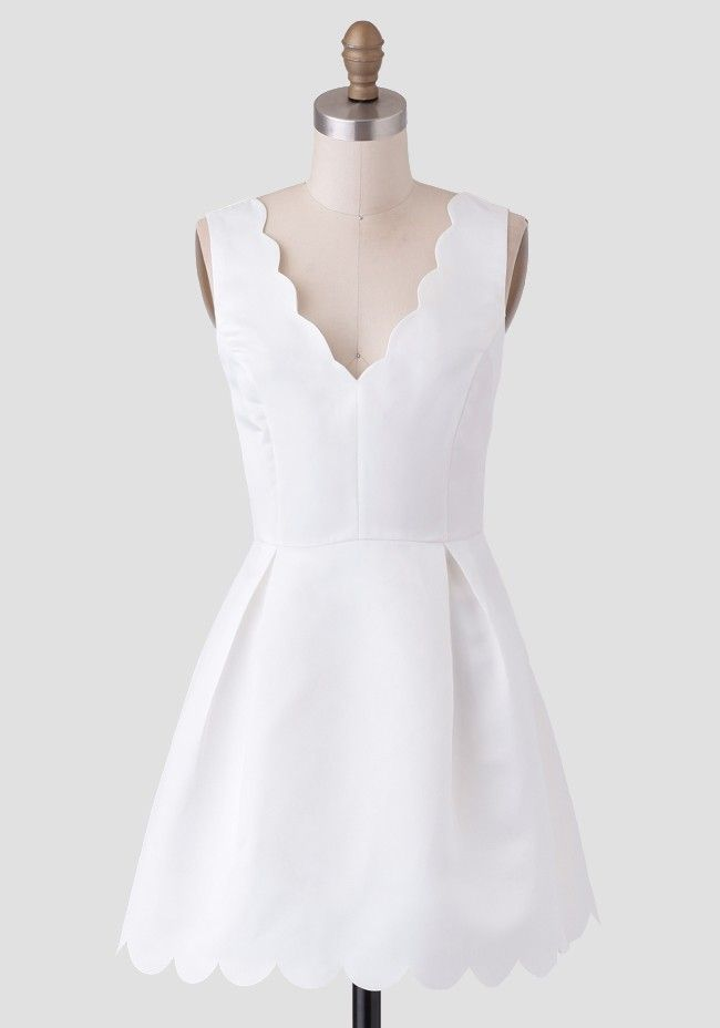 Crafted in a silky-smooth fabric, this stunning white dress features scalloped detailing at the hem and V-cut neckline. Perfected with inverted pleats at the waist and a hidden back zipper, thi...