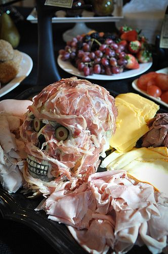Party Meat Head Platter 2 link doesn't give a recipe or instructions, but it looks to me as if there is a honeydew melon carved under there with an bit of food dye across the teeth. Olive eyeballs and marbled deli meat draped around it?