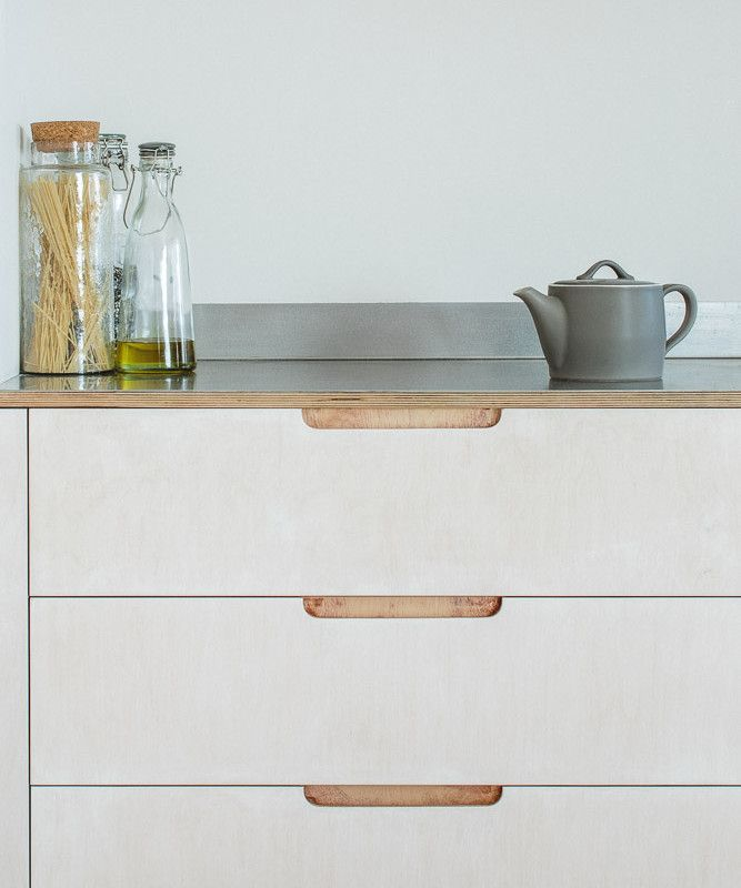 Detail of exposed lye treated plywood drawer cabinet with brushed stainless steel worktop