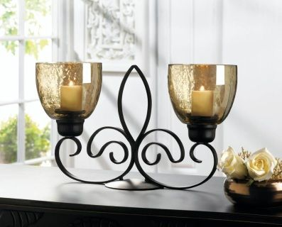 """by Gallery of Light Light up your nights with French flair! This black iron candle holder features a cool fleur-de-lis symbol that stands between two glass candle cups with an iridescent finish. Add the candles of your choice and light them for a beautiful and shimmering table centerpiece. 13"""" x 4.5"""" x 8.25""""  www.allgooddecor.com/shop.html #allgooddecor #decorations #gifts #candles #toys #discount #furniture #candleholders #home #figurines #lighting #pictures #mirrors #jewelry #garden…"""