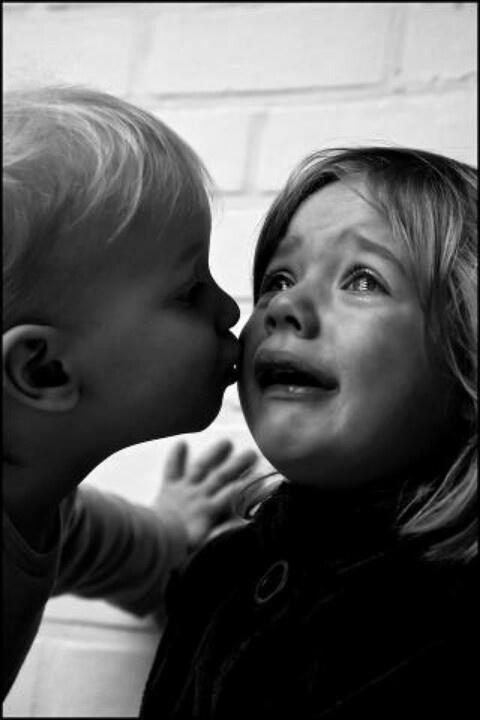 een klein jongetje was een huilend meisje troost door haar een kusje te geven