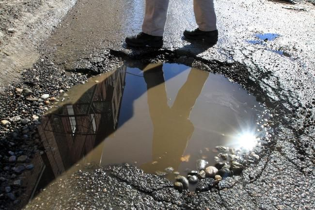 A pedestrian avoids a large pothole on Snow Street in downtown Providence.#RIpothole