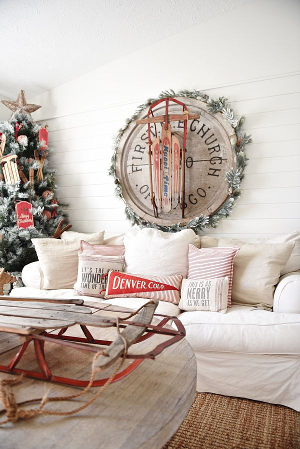 Cottage style Christmas living room - Lovely rustic pops of red with vintage sleds, flocked tree, skis, & more. Great pin for rustic home decor inspiration!