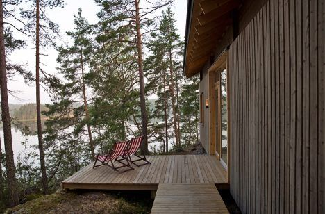 Lake cabin by Sini Kamppari features slatted timber siding and projecting…