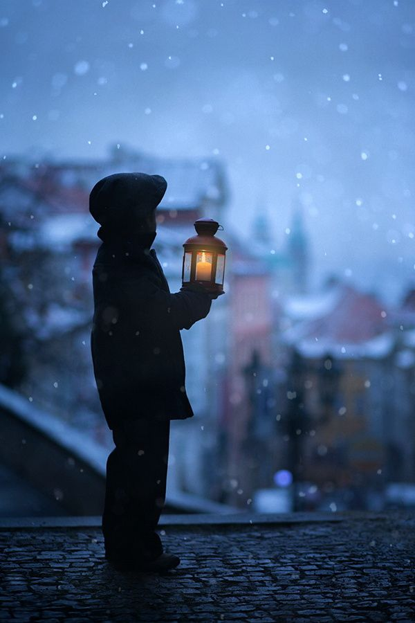 The shadow - Silhouette of boy, standing on stairs, holding lantern, view of Prague behind him, snowy evening