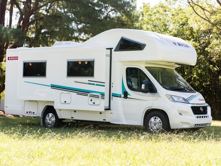 This is a side view of the C7424SL Birdsville motorhome with the slide out room opened. This vehicle is a C Type because it has a bed over the drivers cabin at the front of the vehicle.