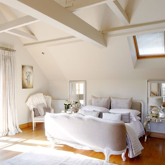 Beams were washed creamy white to maximize the light. An elegant upholstered French bed is the focal point of the bedroom scheme.
