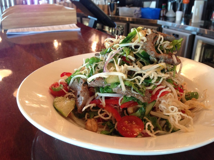 Warm Thai Beef Salad w/ crispy noodles, cherry tomatoes, cashews & spicy dressing (available Gluten Free). Available @ The Quarie