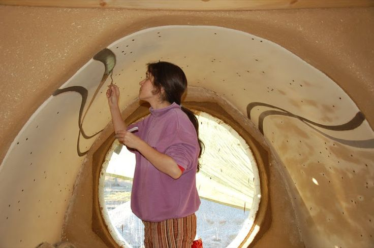 Painting the inside of a straw bale dome.