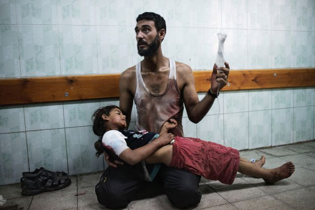 A Palestinian man holds a girl injured during shelling at a U.N.-run school sheltering Palestinians, at a hospital in the northern Gaza Strip on July 24, 2014.